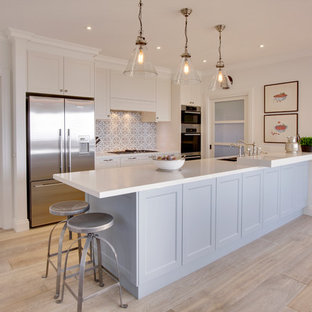 This is an example of a large nautical single-wall kitchen pantry in Melbourne with a double-bowl sink, beaded cabinets, white cabinets, composite countertops, mosaic tiled splashback, stainless steel appliances, plywood flooring and an island.