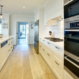 Large beach style single-wall kitchen pantry in Melbourne with a double-bowl sink, beaded cabinets, white cabinets, composite countertops, mosaic tiled splashback, stainless steel appliances, plywood flooring and an island.