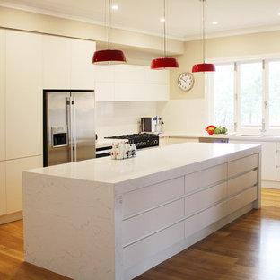 Imagen de cocina moderna, grande, con encimera de vidrio, salpicadero blanco, suelo de madera clara y una isla