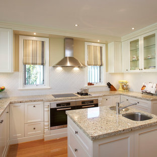 This is an example of a traditional u-shaped kitchen in Perth with an undermount sink, shaker cabinets, white cabinets, granite benchtops, white splashback, porcelain splashback, stainless steel appliances, with island, multi-coloured benchtop and medium hardwood floors.