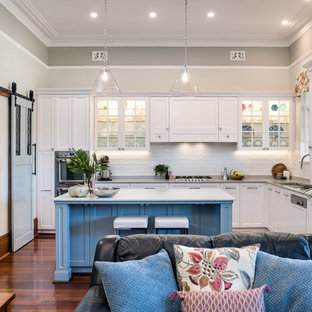 This is an example of a mid-sized transitional l-shaped open plan kitchen in Perth with an undermount sink, shaker cabinets, white cabinets, quartz benchtops, white splashback, ceramic splashback, stainless steel appliances, medium hardwood floors, brown floor, multi-coloured benchtop and multiple islands.