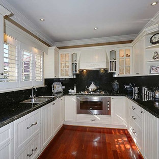 Large country u-shaped eat-in kitchen in Perth with white cabinets, granite benchtops, black splashback, stainless steel appliances, medium hardwood floors, a double-bowl sink, recessed-panel cabinets, stone slab splashback, a peninsula and red floor.