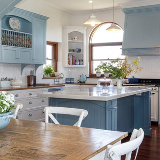 Photo of a traditional u-shaped kitchen in Adelaide with a farmhouse sink, shaker cabinets, white cabinets, white splashback, coloured appliances, dark hardwood floors, with island, brown floor and white benchtop.