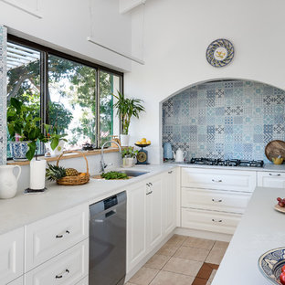 Design ideas for a mid-sized mediterranean l-shaped kitchen in Perth with an undermount sink, solid surface benchtops, blue splashback, ceramic splashback, stainless steel appliances, ceramic floors, with island, white benchtop, raised-panel cabinets, white cabinets and beige floor.