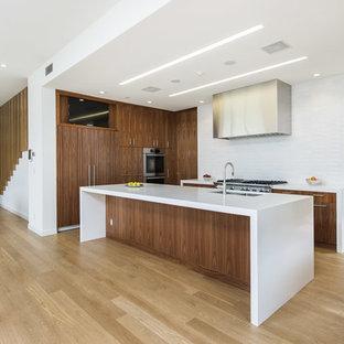 Moderne Küche in U-Form mit Unterbauwaschbecken, flächenbündigen Schrankfronten, dunklen Holzschränken, Küchenrückwand in Weiß, Küchengeräten aus Edelstahl, hellem Holzboden und Kücheninsel in Los Angeles