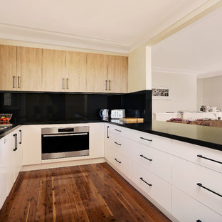 Design ideas for a mid-sized contemporary u-shaped open plan kitchen in Sydney with a drop-in sink, flat-panel cabinets, white cabinets, quartz benchtops, black splashback, stone slab splashback, black appliances, medium hardwood floors, a peninsula, brown floor and black benchtop.