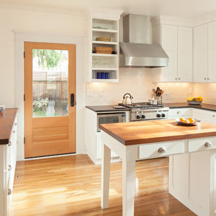 This is an example of an arts and crafts u-shaped separate kitchen in Portland with a farmhouse sink, recessed-panel cabinets, white cabinets, wood benchtops, white splashback, subway tile splashback, stainless steel appliances and medium hardwood floors.