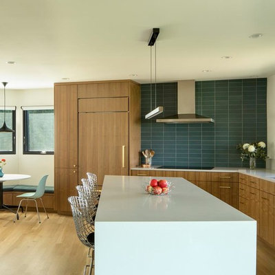 Inspiration for a large 1960s l-shaped medium tone wood floor and brown floor eat-in kitchen remodel in Portland with an undermount sink, flat-panel cabinets, medium tone wood cabinets, green backsplash, paneled appliances, an island, quartz countertops, porcelain backsplash and white countertops