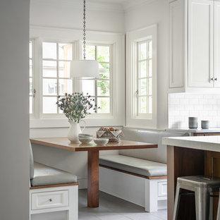 Inredning av ett maritimt stort vit vitt kök och matrum, med skåp i shakerstil, vita skåp, bänkskiva i kvarts, vitt stänkskydd, stänkskydd i tunnelbanekakel, klinkergolv i keramik, en köksö och grått golv