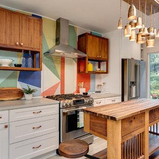 ロサンゼルスのエクレクティックスタイルのおしゃれなアイランドキッチン (シェーカースタイル扉のキャビネット、白いキャビネット、木材カウンター、ガラス板のキッチンパネル、シルバーの調理設備の、ベージュの床、茶色いキッチンカウンター) の写真