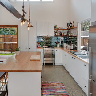 Industrial l-shaped open plan kitchen in Sunshine Coast with a double-bowl sink, flat-panel cabinets, white cabinets, wood benchtops, green splashback, subway tile splashback, stainless steel appliances and with island.