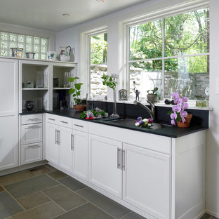 Inspiration for a medium sized contemporary l-shaped kitchen pantry in Philadelphia with a submerged sink, recessed-panel cabinets, white cabinets, blue splashback, stone slab splashback, black appliances and slate flooring.
