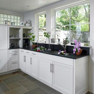 Immagine di una cucina minimal di medie dimensioni con lavello sottopiano, ante con riquadro incassato, ante bianche, paraspruzzi blu, paraspruzzi in lastra di pietra, elettrodomestici neri e pavimento in ardesia