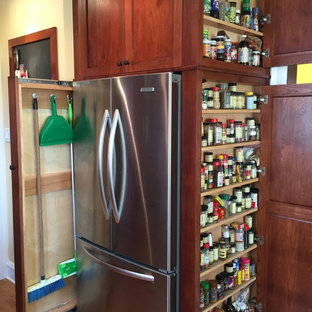 シカゴの中サイズのトラディショナルスタイルのおしゃれなアイランドキッチン (シェーカースタイル扉のキャビネット、中間色木目調キャビネット、珪岩カウンター、シルバーの調理設備、無垢フローリング) の写真