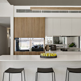 Design ideas for a mid-sized contemporary single-wall eat-in kitchen in Canberra - Queanbeyan with an undermount sink, flat-panel cabinets, white cabinets, quartz benchtops, metallic splashback, mirror splashback, black appliances, concrete floors, with island, grey floor and white benchtop.