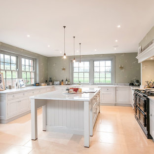 This is an example of a large country l-shaped kitchen in Hampshire with white cabinets, granite worktops, white splashback, stone slab splashback, black appliances, porcelain flooring, an island, beige floors and shaker cabinets.