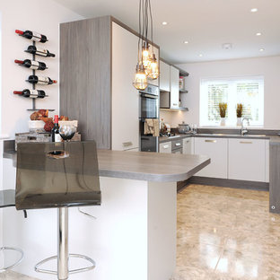 Design ideas for a contemporary u-shaped kitchen in Kent with flat-panel cabinets, white cabinets, a breakfast bar and beige floors.