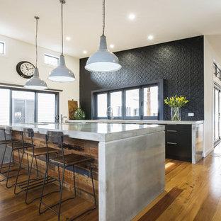 Idee per una cucina minimal di medie dimensioni con lavello sottopiano, ante lisce, ante nere, top in cemento, paraspruzzi nero, paraspruzzi con piastrelle di metallo, elettrodomestici in acciaio inossidabile, pavimento in legno massello medio e isola