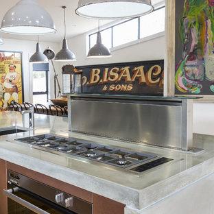 Inspiration för mellanstora moderna linjära kök med öppen planlösning, med en undermonterad diskho, släta luckor, svarta skåp, bänkskiva i betong, svart stänkskydd, stänkskydd i metallkakel, rostfria vitvaror, mellanmörkt trägolv och en köksö