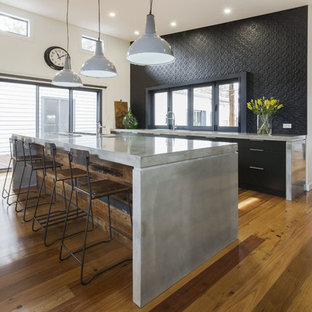 Photo of a mid-sized contemporary single-wall open plan kitchen in Sydney with an undermount sink, flat-panel cabinets, black cabinets, concrete benchtops, black splashback, metal splashback, stainless steel appliances, medium hardwood floors and with island.