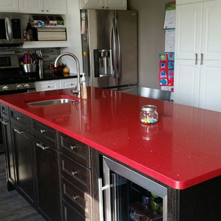This is an example of a medium sized contemporary l-shaped kitchen/diner in Toronto with a submerged sink, shaker cabinets, white cabinets, engineered stone countertops, multi-coloured splashback, matchstick tiled splashback, stainless steel appliances, porcelain flooring, an island and red worktops.