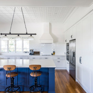 This is an example of a country u-shaped eat-in kitchen in Gold Coast - Tweed with a farmhouse sink, shaker cabinets, white cabinets, white splashback, subway tile splashback, stainless steel appliances, medium hardwood floors, with island, brown floor and white benchtop.