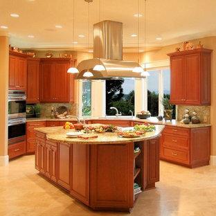 Inredning av ett klassiskt mycket stort gul gult kök, med rostfria vitvaror, luckor med upphöjd panel, skåp i mellenmörkt trä, granitbänkskiva, stänkskydd i sten, en undermonterad diskho, travertin golv, en köksö, gult stänkskydd och gult golv