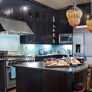 他の地域のエクレクティックスタイルのおしゃれなキッチン (シルバーの調理設備、ドロップインシンク、シェーカースタイル扉のキャビネット、御影石カウンター、ガラスタイルのキッチンパネル、黒いキャビネット、青いキッチンパネル、無垢フローリング、茶色い床) の写真
