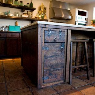 ダラスの中くらいのおしゃれなキッチン (シェーカースタイル扉のキャビネット、濃色木目調キャビネット、人工大理石カウンター、マルチカラーのキッチンパネル、モザイクタイルのキッチンパネル、シルバーの調理設備、テラコッタタイルの床、赤い床) の写真
