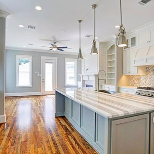 Mid-sized traditional galley open plan kitchen in Houston with a single-bowl sink, recessed-panel cabinets, white cabinets, granite benchtops, grey splashback, glass tile splashback, stainless steel appliances, plywood floors, with island and brown floor.