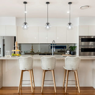 This is an example of a contemporary galley kitchen in Central Coast with beaded inset cabinets, beige cabinets, stainless steel appliances, medium hardwood floors, brown floor and beige benchtop.
