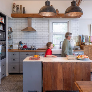 Photo of a country kitchen in Sydney with white splashback, with island and multi-coloured benchtop.