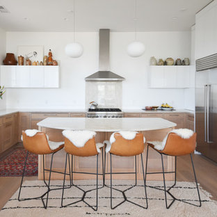 Inspiration for a scandinavian u-shaped kitchen in Portland Maine with an undermount sink, flat-panel cabinets, white cabinets, beige splashback, stone slab splashback, stainless steel appliances, light hardwood floors, with island and beige benchtop.