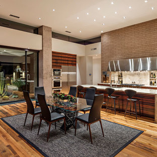 Southwestern eat-in kitchen inspiration - Southwest l-shaped medium tone wood floor and brown floor eat-in kitchen photo in Phoenix with an undermount sink, flat-panel cabinets, dark wood cabinets, beige backsplash, stone slab backsplash, stainless steel appliances, an island and gray countertops