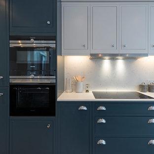 ロンドンの中くらいのヴィクトリアン調のおしゃれなキッチン (ドロップインシンク、シェーカースタイル扉のキャビネット、青いキャビネット、人工大理石カウンター、白いキッチンパネル、大理石のキッチンパネル、黒い調理設備、淡色無垢フローリング、アイランドなし、ベージュの床) の写真