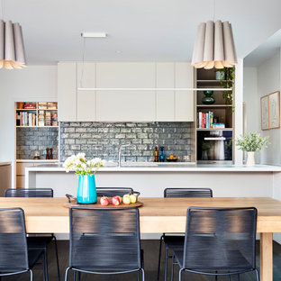 Inspiration for a large contemporary l-shaped kitchen in Melbourne with an undermount sink, flat-panel cabinets, grey splashback, stainless steel appliances, multiple islands, brown floor and white benchtop.