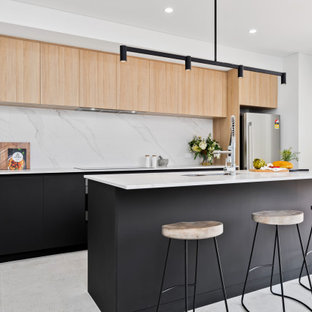 Photo of a mid-sized scandinavian galley kitchen in Perth with an undermount sink, flat-panel cabinets, black cabinets, white splashback, stainless steel appliances, porcelain floors, with island, grey floor and white benchtop.