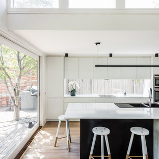 Inspiration for a modern galley kitchen in Melbourne with a drop-in sink, flat-panel cabinets, white cabinets, window splashback, stainless steel appliances, medium hardwood floors, with island, brown floor and white benchtop.