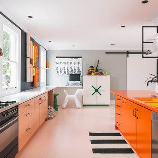 他の地域のコンテンポラリースタイルのおしゃれなアイランドキッチン (アンダーカウンターシンク、ラミネートカウンター、白いキッチンパネル、セラミックタイルのキッチンパネル、黒い調理設備、塗装フローリング、ピンクの床、オレンジのキッチンカウンター) の写真