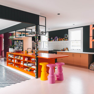 This is an example of an eclectic kitchen in Other with an undermount sink, laminate benchtops, white splashback, ceramic splashback, black appliances, painted wood floors, with island, pink floor and orange benchtop.