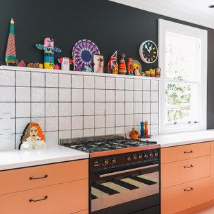 Стильный дизайн: кухня в современном стиле с врезной раковиной, столешницей из ламината, белым фартуком, фартуком из керамической плитки, черной техникой, деревянным полом, островом, розовым полом и оранжевой столешницей - последний тренд