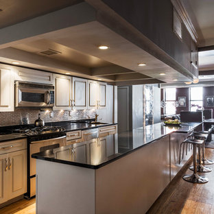 This is an example of a mid-sized industrial galley eat-in kitchen in New York with a single-bowl sink, louvered cabinets, grey cabinets, quartz benchtops, metallic splashback, ceramic splashback, stainless steel appliances, medium hardwood floors, with island and black benchtop.