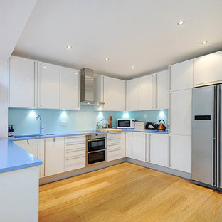 Large modern eat-in kitchen designs - Eat-in kitchen - large modern single-wall slate floor eat-in kitchen idea in London with a single-bowl sink, open cabinets, blue cabinets, quartzite countertops, blue backsplash, glass tile backsplash, colored appliances and an island
