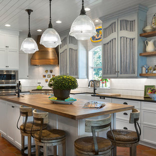 Coastal kitchen designs - Inspiration for a coastal l-shaped terra-cotta tile and orange floor kitchen remodel in Charlotte with a farmhouse sink, recessed-panel cabinets, white cabinets, white backsplash, stainless steel appliances, an island and black countertops