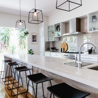 Inspiration for a large contemporary galley kitchen in Melbourne with an undermount sink, flat-panel cabinets, white cabinets, beige splashback, stainless steel appliances, an island and medium hardwood floors.