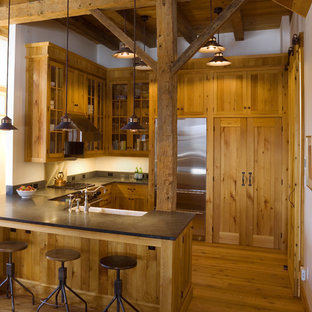 Example of a mountain style u-shaped open concept kitchen design in Burlington with a farmhouse sink, glass-front cabinets, medium tone wood cabinets and stainless steel appliances