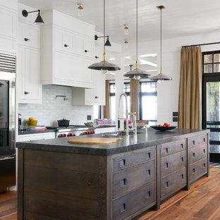 トロントのビーチスタイルのおしゃれなアイランドキッチン (アンダーカウンターシンク、シェーカースタイル扉のキャビネット、白いキャビネット、白いキッチンパネル、サブウェイタイルのキッチンパネル、シルバーの調理設備の、無垢フローリング、オレンジの床) の写真