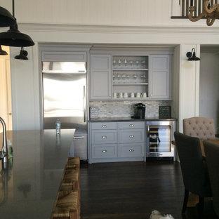 トロントの大きいシャビーシック調のおしゃれなキッチン (アンダーカウンターシンク、シェーカースタイル扉のキャビネット、グレーのキャビネット、クオーツストーンカウンター、磁器タイルのキッチンパネル、シルバーの調理設備の、濃色無垢フローリング) の写真