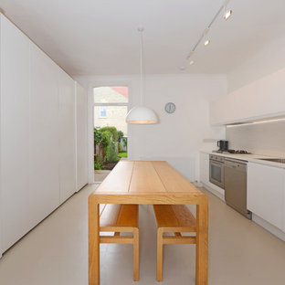 Medium sized contemporary galley kitchen/diner in London with a single-bowl sink, recessed-panel cabinets, white cabinets, laminate countertops, white splashback, ceramic splashback, stainless steel appliances, lino flooring, no island, beige floors and white worktops.
