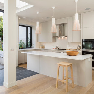 Photo of a scandinavian kitchen in London with with island, flat-panel cabinets, quartz benchtops, stainless steel appliances, an undermount sink, light hardwood floors and grey cabinets.